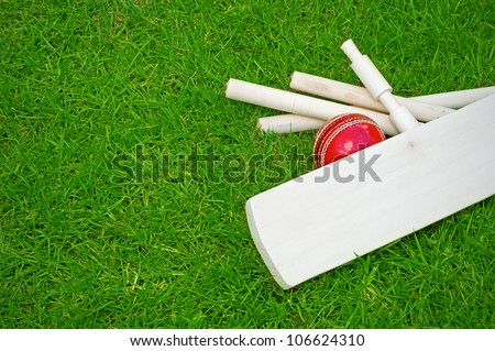 cricket set including ball, bat and stumps on green grass pitch with copy space - stock photo