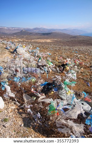 CRIKVENICA, CROATIA - MARCH 8, 2015: Discarded plastic shopping bags blown by wind  from an unguarded garbage disposal facility, polluting meadows on a hill slope in Croatia.
