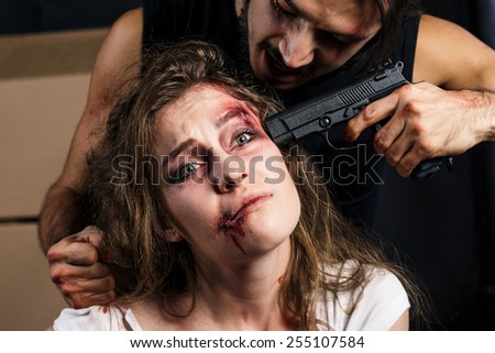 Crime. Beautiful girl kidnapped by criminals. Terrorist is threatening hostages with a gun. - stock photo