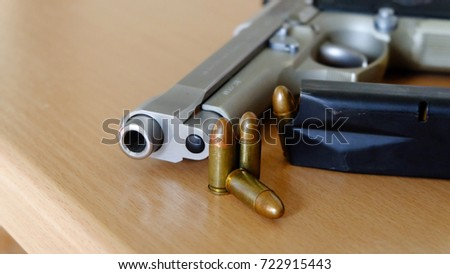 Crime concept,Gun and bullets place on the desk.