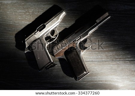 Crime concept. Pair of pistols on dark background under beam of light
