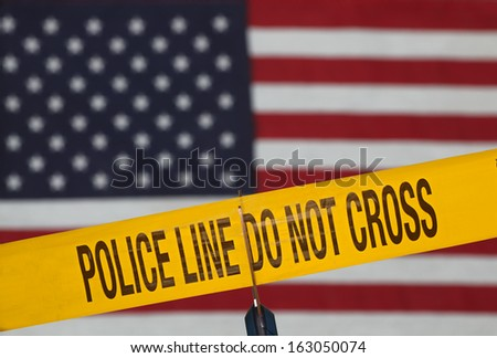 Crime scene barrier tape over out of focus US flag being cut with scissors
