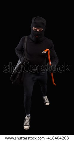Crime scene - criminal thief or burglar man in balaclava or mask covering face holding crowbar in hand for break opening home door lock. Isolated on black. - stock photo