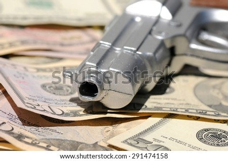 Crime scene image: Gun muzzle on a pile of US Dollars banknotes - stock photo