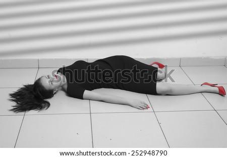 Crime scene imitation. Lifeless business woman lying on the floor - stock photo