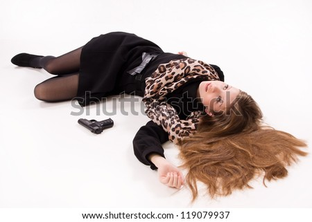 Crime scene imitation. Spy girl with gun lying on the floor