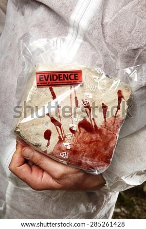 Crime scene investigation - evidence in hands - stock photo