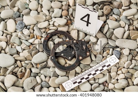 Crime scene investigation. Handcuffs dragged along outdoors on the beach - stock photo