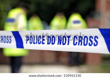 Crime scene investigation police do not cross boundary tape investigating police team - stock photo