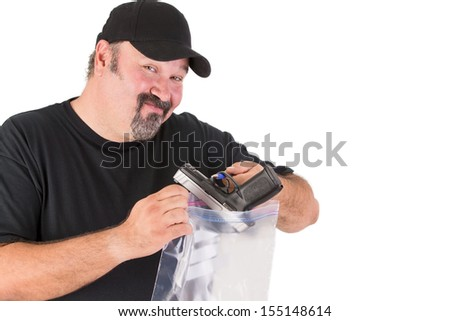 Crime scene investigator founds a gun, he has a sure look on his face while he is placing gun in to a evidence bag - stock photo