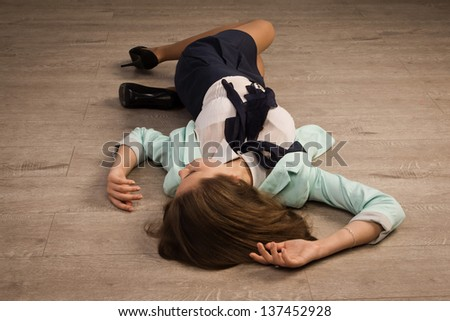Crime scene simulation: college girl lying on the floor - stock photo