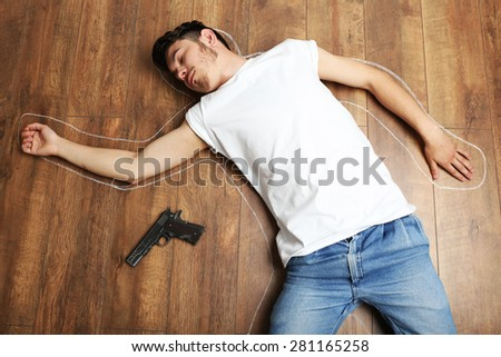Crime scene simulation, young man lying with gun on floor - stock photo