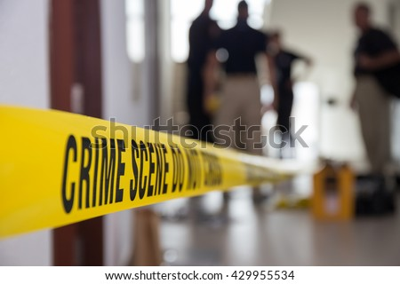 crime scene tape in building with blurred forensic team background - stock photo