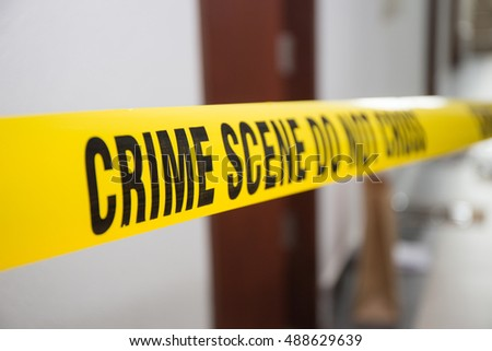 crime scene tape in front of room door with blurred background