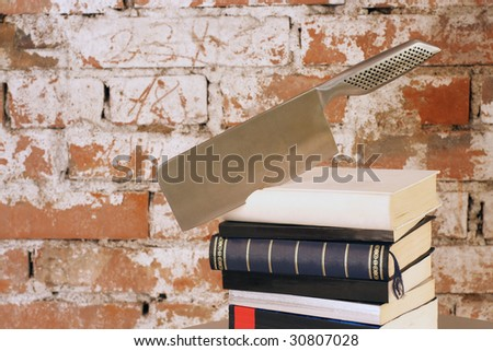 Crime Story: Axe shaped knife stuck in books. - stock photo