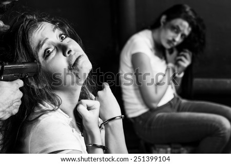 Crime. Two beautiful girls in the Business clothing kidnapped by criminals. Terrorist is threatening hostages with a gun. - stock photo