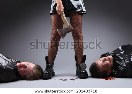 Crime. Woman power and feminism concept. A woman with an axe covered in blood, two men lying down next to her feet. Dominancy of women over men. Matriarchy. - stock photo