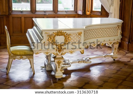 CRIMEA, RUSSIA - SEPTEMBER 25, 2014:White vintage beautifully decorated grand piano stands in middle of living room. Interiors of halls in Vorontsov Palace in Alupka. The palace is built in 1848. - stock photo