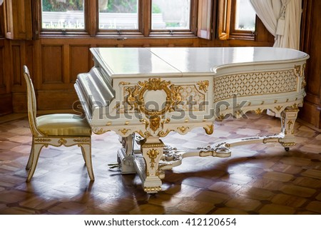 CRIMEA, RUSSIA - SEPTEMBER 25, 2014: White vintage beautifully decorated grand piano stands in the middle of the living room
