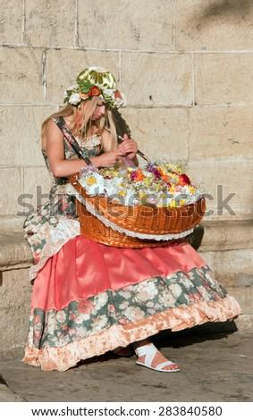 CRIMEA, SEVASTOPOL, JUNE 13, 2014: Beautiful girl in vintage dress selling flowers - stock photo