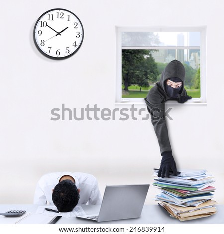 Criminal activity concept with male bandit wearing mask and steal corporate documents through the window - stock photo