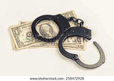 Criminal. Close up of handcuffs on money - stock photo