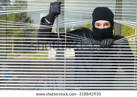Criminal concept. Burglar in front of window behind jalousie holds knife in hand. - stock photo