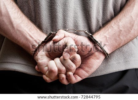 Criminal hands locked in handcuffs. Close-up view - stock photo