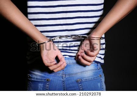 Criminal hands locked in handcuffs on dark background - stock photo