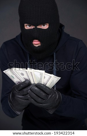 Criminal in a balaclava holding a fistful of money conceptual of the loot from a robbery bribe corruption coercion payoff ransom or mob protection money - stock photo