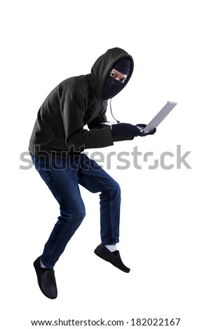 Criminal in dark clothes and balaclava is stealing a laptop computer