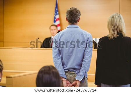 Criminal waiting for courts ruling in the court room - stock photo