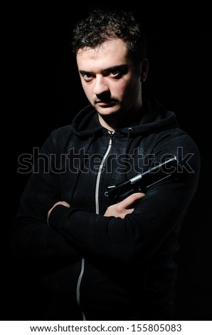 Criminal with gun against a black background