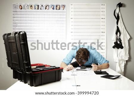 Criminologist at work on fingerprint identification - stock photo