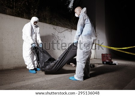 Criminology technicians leaving place of found with body in bag - stock photo