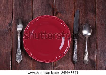 Crimson empty plate with cutlery. Table setting. Fork, knife and spoon on the table. Space for text. - stock photo
