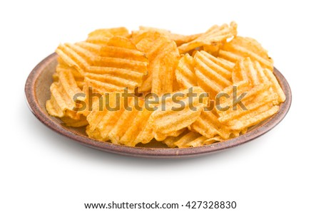 Crinkle cut potato chips isolated on white background. Tasty spicy potato chips on plate. - stock photo