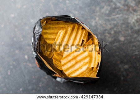 Crinkle cut potato chips on kitchen table. Tasty spicy potato chips in bag. Top view. - stock photo