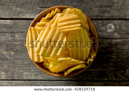 Crinkle cut potato chips on kitchen table. Tasty spicy potato chips in bowl. Top view. - stock photo