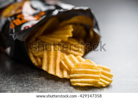 Crinkle cut potato chips on old kitchen table. Potato chips poured out from packing. - stock photo