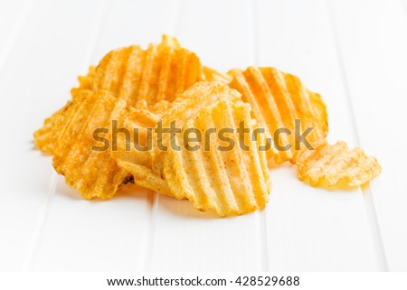 Crinkle cut potato chips on table. Tasty spicy potato chips. - stock photo