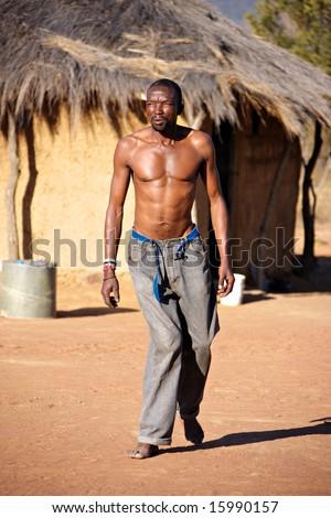 Crippled African man walking barefoot in the hot sand of Kalahari - stock photo
