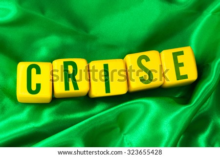 Crise (Crisis in Portuguese) written on yellow cube on green background - stock photo