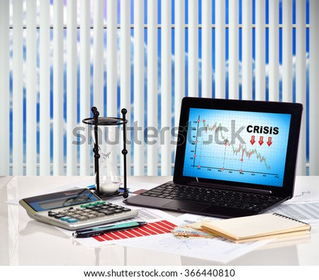 Crisis chart on screen notebook. Financial and business charts and report on table - stock photo