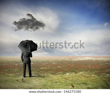 Crisis concept with businessman under a black cloud - stock photo
