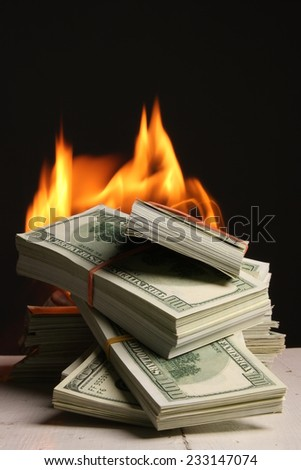 Crisis. dollars in fire, burning dollar, ashes - stock photo