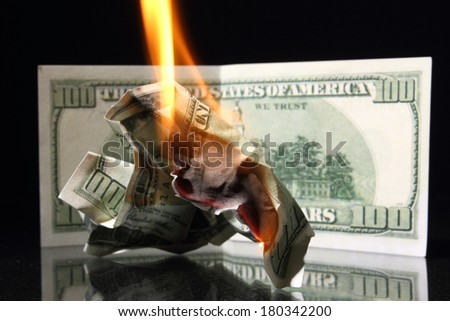 Crisis One hundred dollars in fire, burning dollar, ashes - stock photo