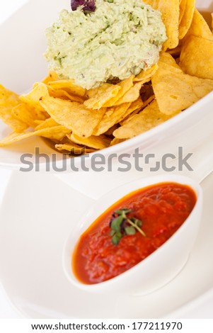 Crisp corn nachos with spicy fresh guacamole sauce and a topping of avocado served as a snack or appetizer in a white bowl