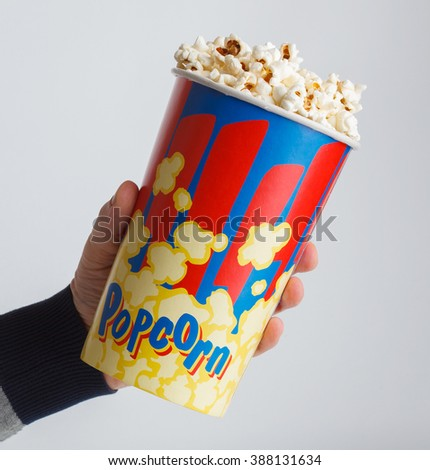 crisp fresh popcorn in a box in his hand on a gray background - stock photo