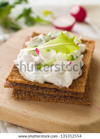 Crisp with cottage cheese, fresh cucumber and radish for healthy breakfast, selective focus - stock photo